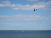 Spitfire does flyby over regatta boats