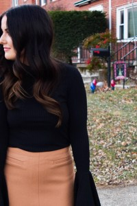 Black flair sleeved top and beige skirt