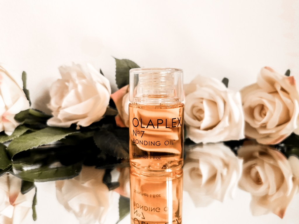 Bottle of Olaplex No.7 surrounded by flowers