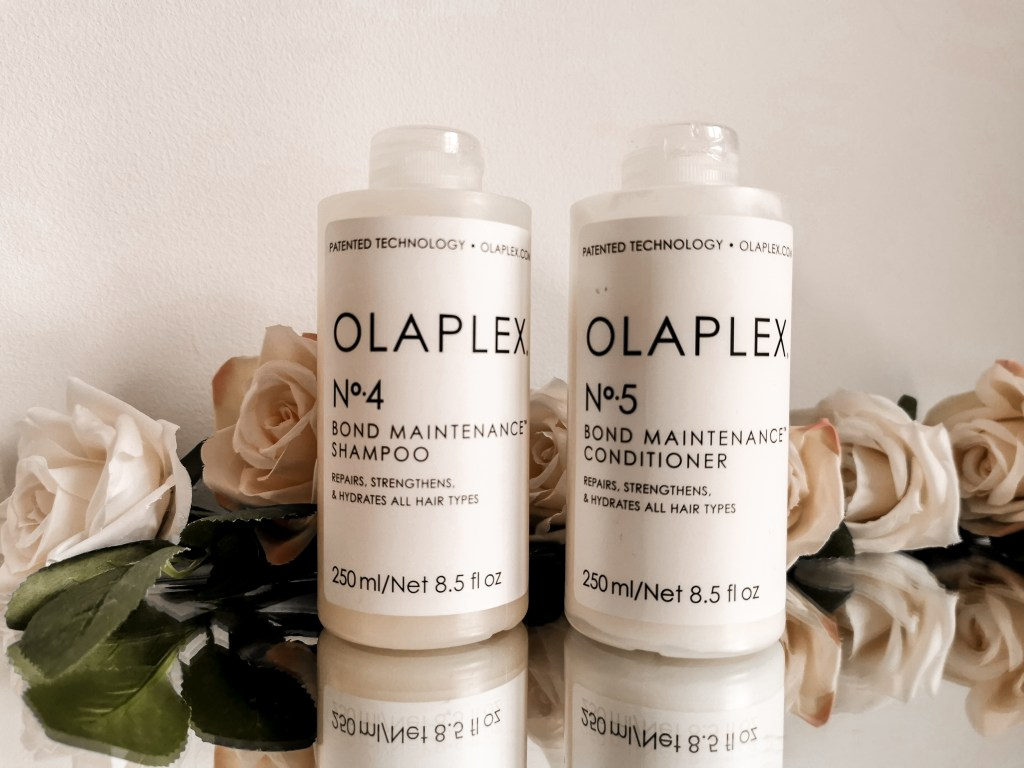 One bottle of Olaplex No.4 and one bottle of Olaplex No.5 surrounded by flowers