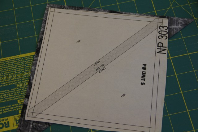 """Take one of your triangles from your 8 1/2"""" squares and lightly glue the WRONG side of the fabric to the WRONG side of the paper."""