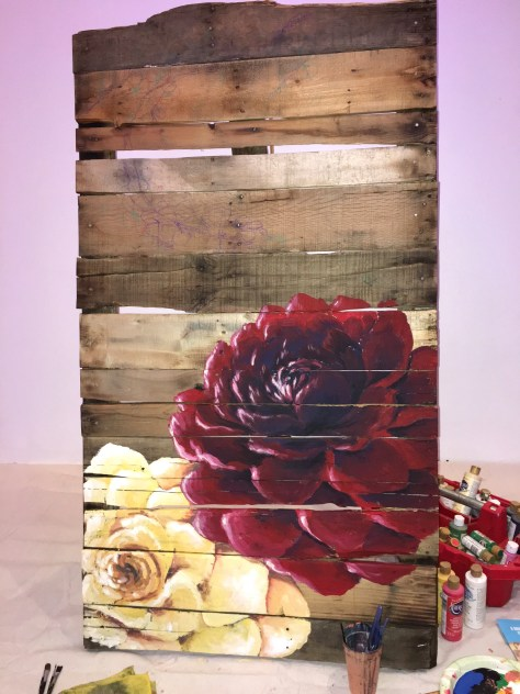 The artist was painting on repurposed wood at the event