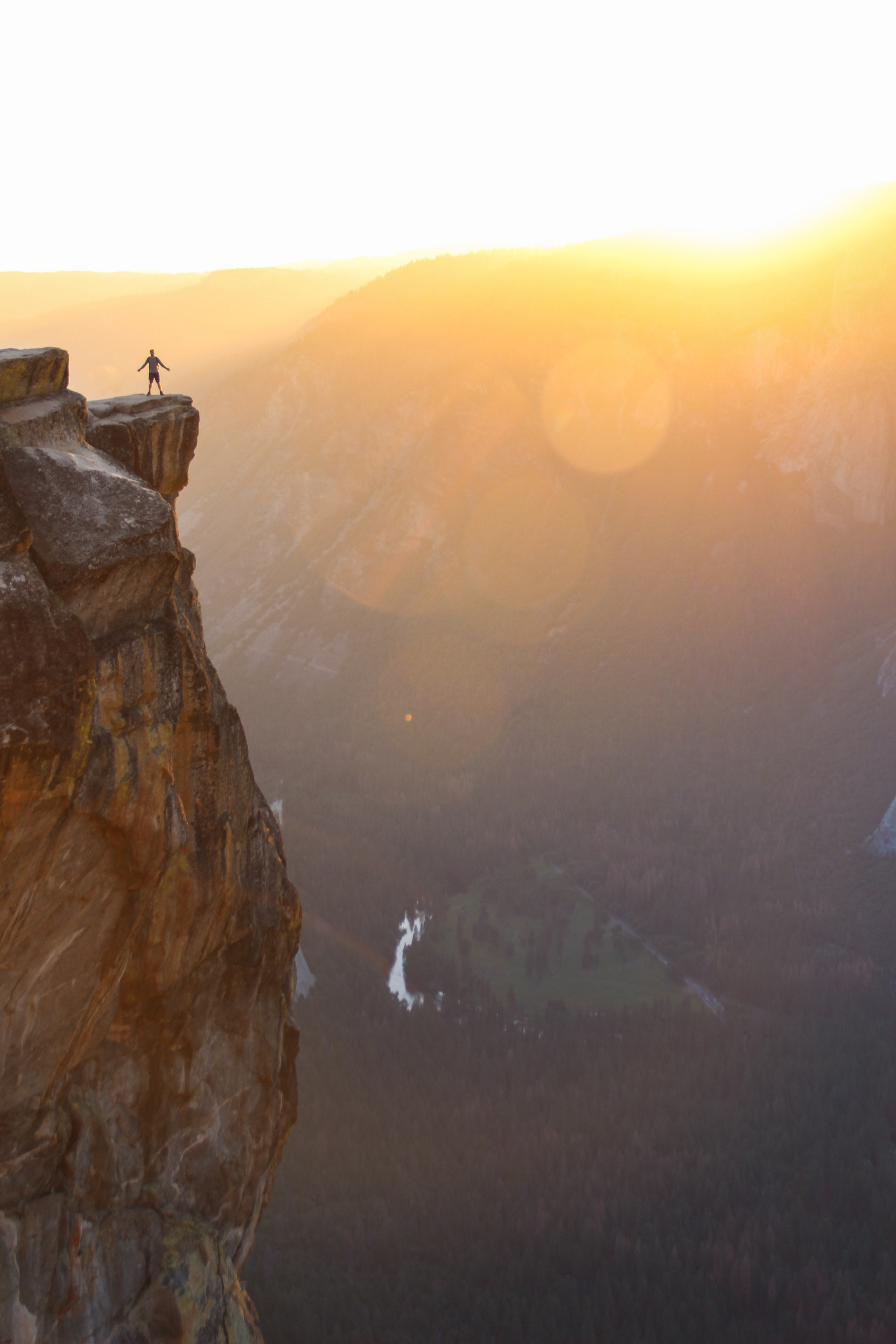 silhouette of person standing on cliff during sunset