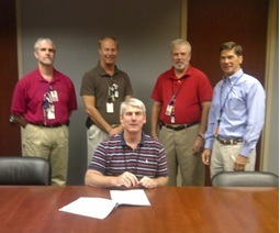 Callaway officials celebrate the signing of the Dry Storage contract: foreground: Mr. Cleve Reasoner, VP Engineering; from left to right: Mr. Steve Ewens, Project Manager; Mr. Shannon Abel, Manager, Major Projects; Mr. Tim Pettus, Supervisor, Major Projects; and Mr. Jay Skitt, Strategic Sourcing Analyst