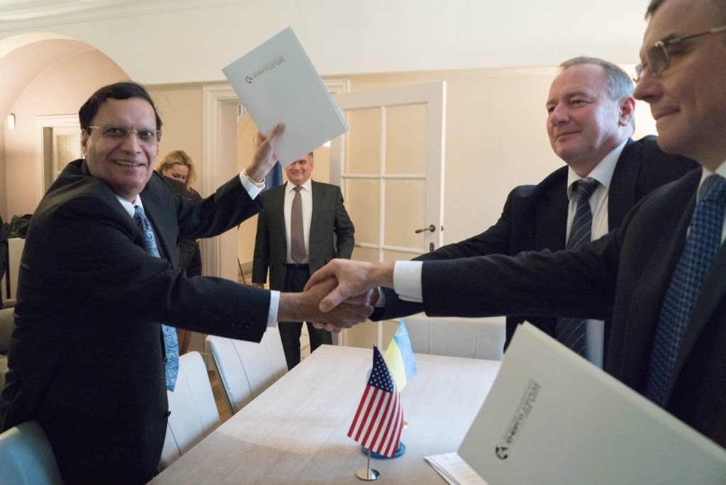 (From Left to Right in the Foreground) Dr. Kris Singh of Holtec, President Nedashkovsky of Energoatom, and General Director Subotin of Turboatom Clasp Hands to Mark the MOU Signing Event