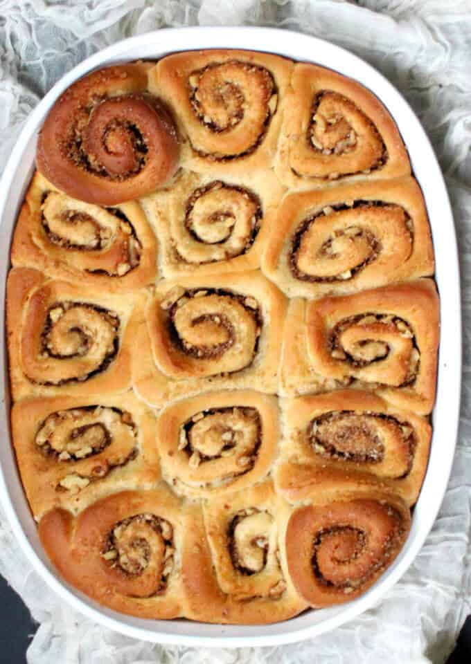 Top shot of cinnamon puns packed with cinnamon sugar and walnuts in a white baking dish