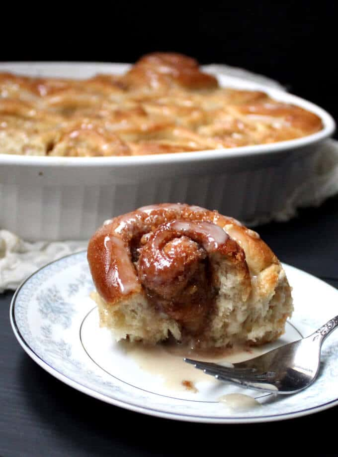 Front shot of a fluffy, half-eaten cinnamon bun on a blue and white china plate with a tray of cinnamon buns in the background