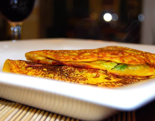 Two besan chilla or cheela, vegan omelets made with chickpea flour, in a white plate