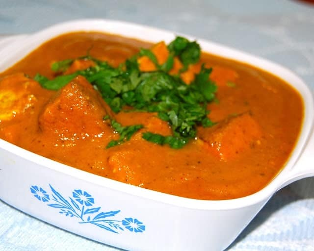 Side shot of Tofu Makhani Curry in a white dish, with tofu and cilantro - holycowvegan.net