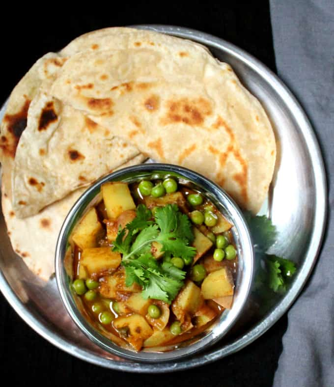 A top shot of aloo matar, peas and potatoes curry with chapati flatbread in a steel thali