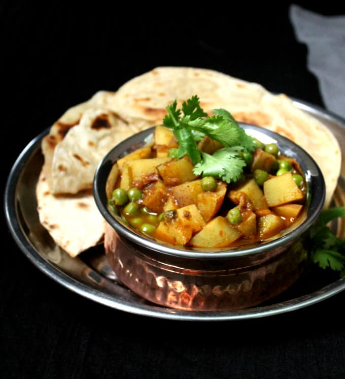 Frontal shot of a bowl of aloo matar with rotis or chapatis against a black background