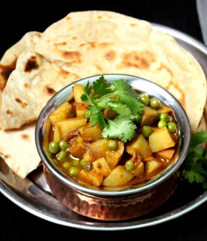 A close up shot of Aloo Matar in a copper and steel handi with rotis in the background on a steel plate