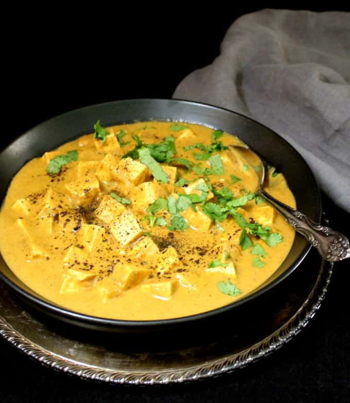 A front partial shot of a bowl of creamy paneer tofu kalmirch on a silver server with a silver serving spoon in the bowl and a gray napkin on the side.