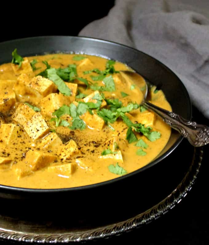 A black bowl with Tofu Paneer Kalimirch, or tofu cubes in a spicy black pepper curry sauce with a gray napkin on the side