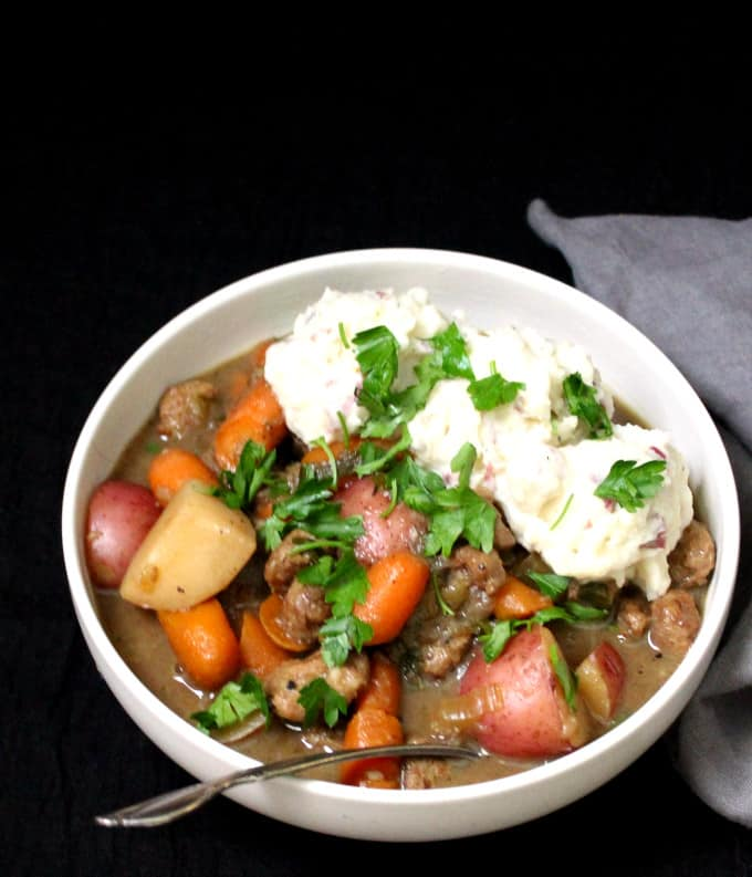A frontal shot of vegan Irish lamb stew against a black background