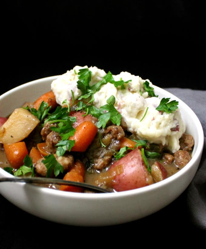 A close side shot of a bowl of vegan Irish stew with carrots, celery, potatoes and mashed potatoes and a spoon against a black background