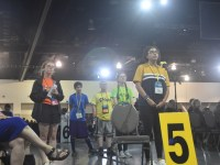 A teenage girl stands at a microphone, with four other youth visible behind her, addressing General Synod.