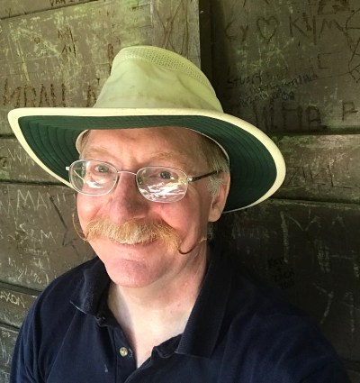 Photo of Pastor Eric in a hiker's hat, smiling but clearly very tired.