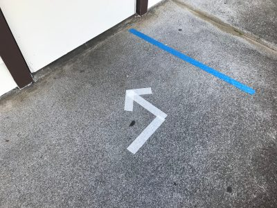 Directional arrows and spacing tape on a walkway.
