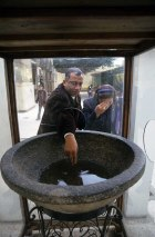 Photo: Norbert Schiller, pilgrims touch the water inside a large granite bowl that the Virgin Mary is said to have baked bread in. The bowl sits in the church courtyard at Samannud and pilgrims come to this site to get blessings from a number of objects, including the bowl.