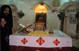 Photo: Norbert Schiller, a priest at the altar inside the Church of St. John the Short at Dayr Abu Hinnis.