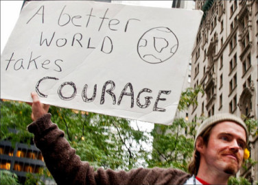 "moral courage, man holding sign stating ""a better world takes courage"""