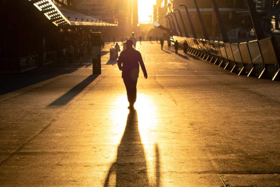 silhouetted figure walking on a city street in the bright light of sunset.