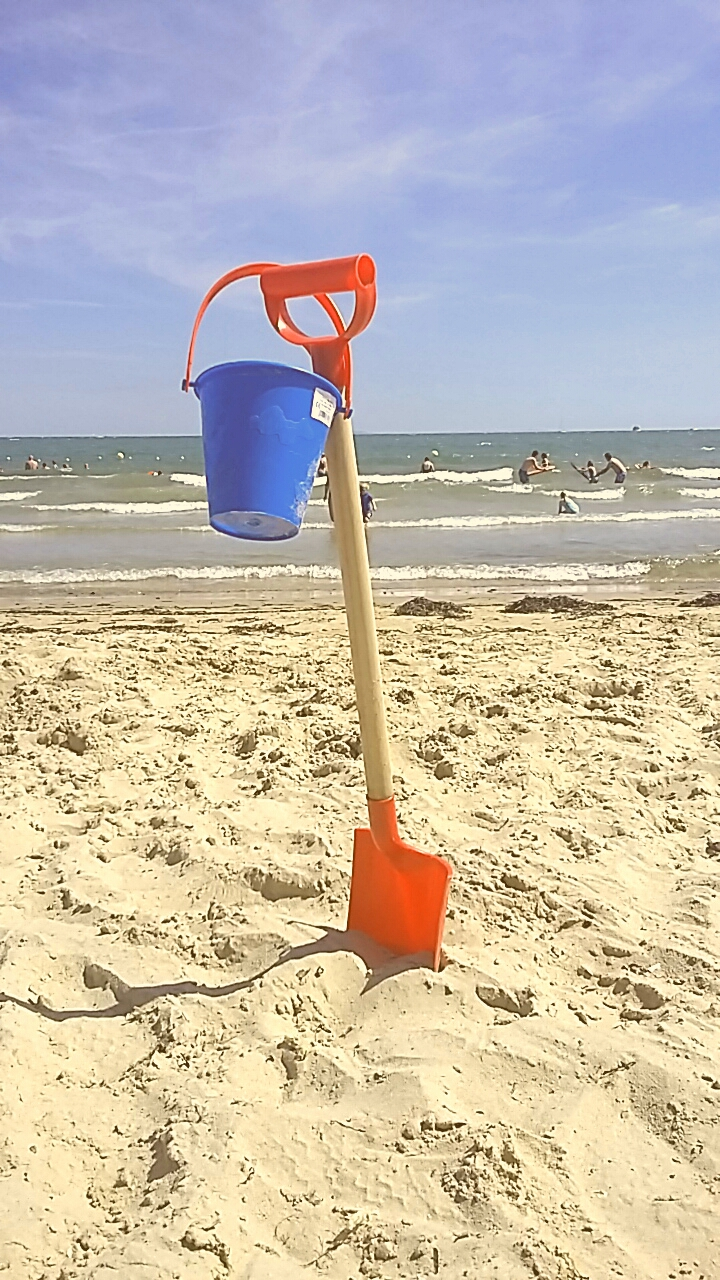 A bucket and spade stood in a sandy beach