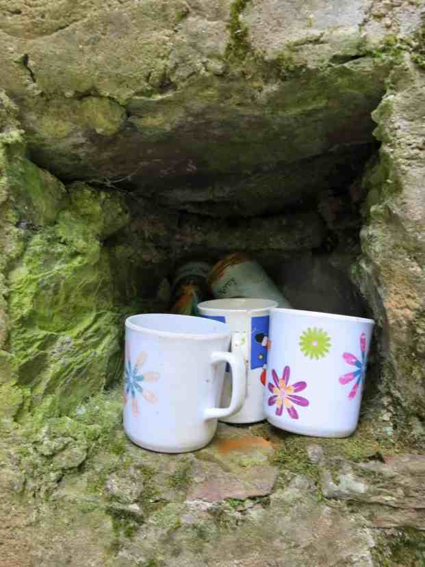Cups are held in a little niche inside the wellhouse