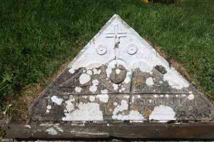 A cross & rosettes above the cherub