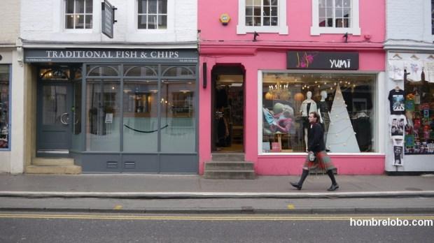Escocés con su kilt frente a tiendas de moda y de Fish & Chips