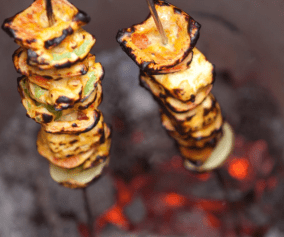 skewered vegetables being lowered into tandoor oven