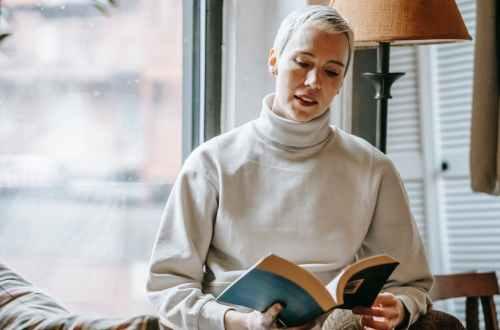 woman reading interesting book near window