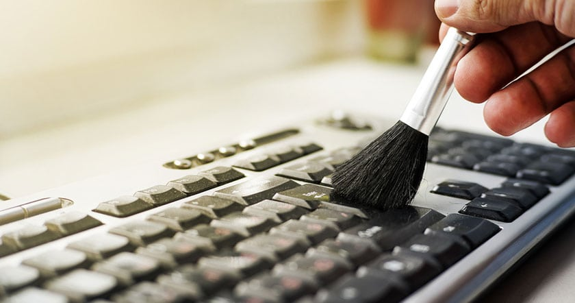 Photo of a Hand Dusting a Keyboard with a Brush