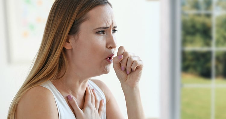 Photo of a Woman Coughing Inside a Room