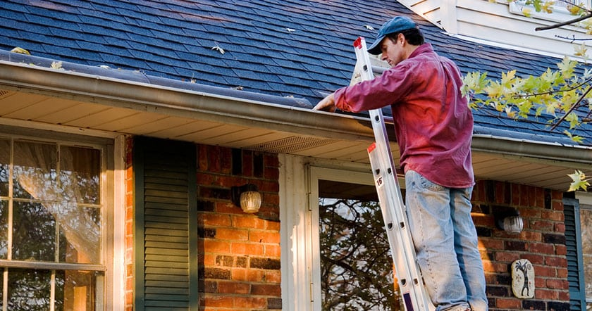 Photo of man cleaning out gutters