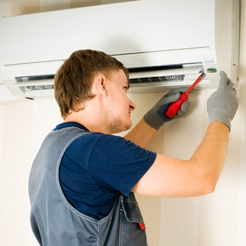 Photo of man installing a ductless mini split air conditioner