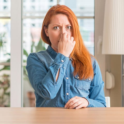 Photo of a woman smelling an odor