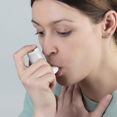 Air Purifiers for Asthma Reviews Woman Using Inhaler