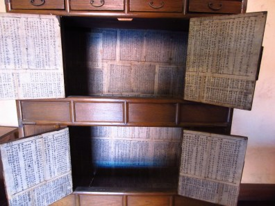 An old colonial cupboard lined with Chinese newsprint.