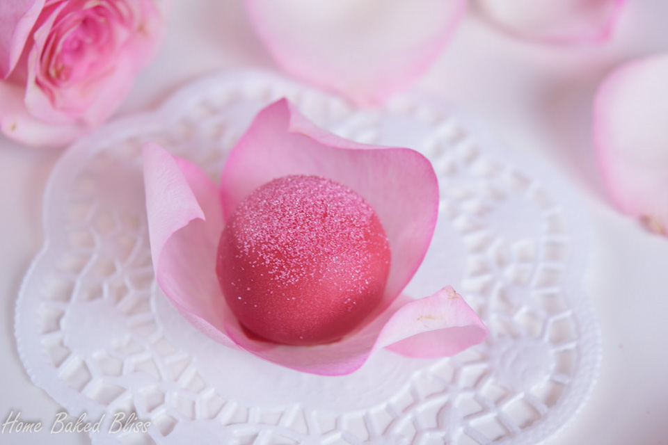 A rose water truffle nestled in rose petals.