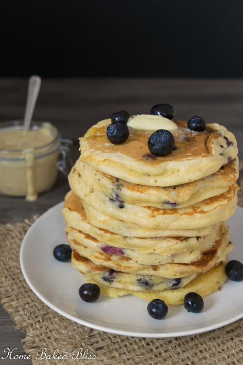 A stack of Blueberry Pancakes next to a jar of Homemade Vanilla Sauce