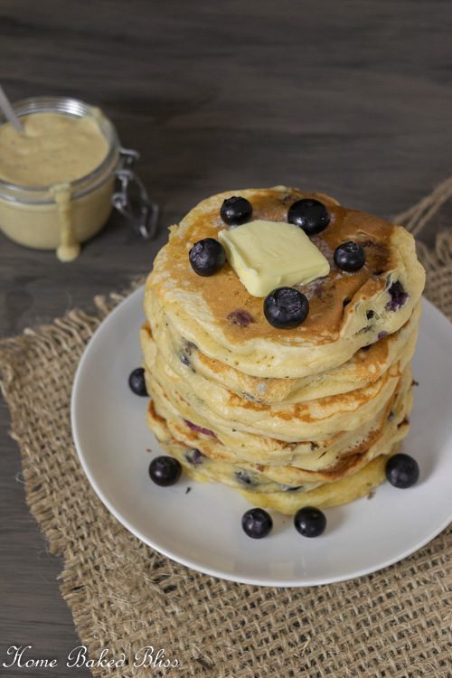 Blueberry Pancakes with Homemade Vanilla Sauce garnished with a dab of butter and fresh blueberries