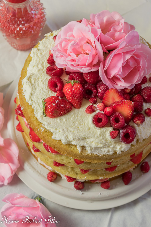 Berry Layer Cake garnished with fresh berries and roses