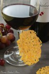 A crispy cheese cracker leaning against a glass of red wine