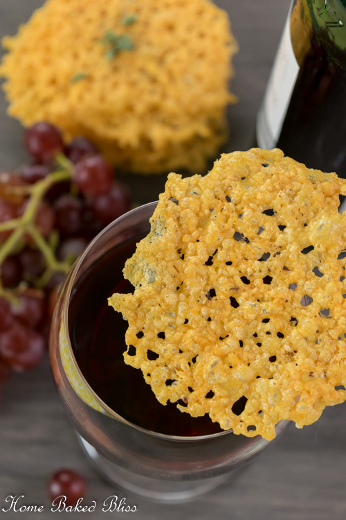 A crispy cheese cracker sitting on top of a glass of red wine.
