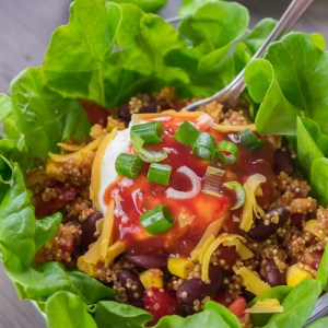 Southwestern Quinoa Salad in a glass bowl garnished with salsa and green onions.