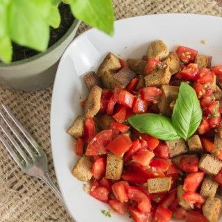 Panzanella (Italian Bread Salad) in a white bowl garnished with fresh basil.