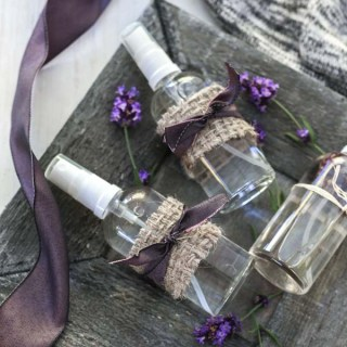 Three bottles of lavender linen spray on a wooden plate next to a purple ribbon and lavender buds.