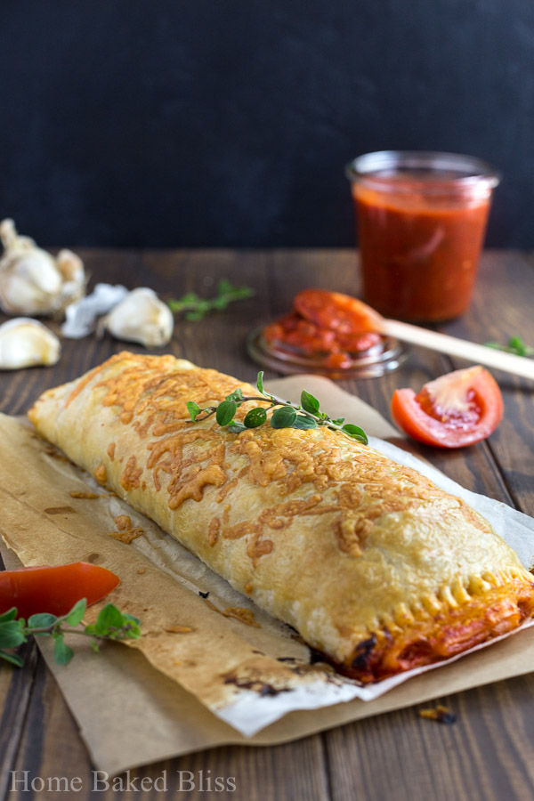 Cheesy calzone on wooden background next to jar of marinara sauce.